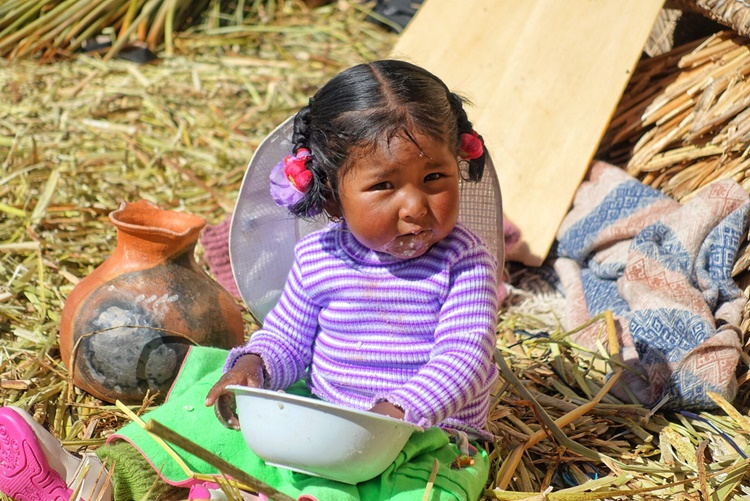 A Peruvian child quietly munches on breakfast on the floating island Uros in Lake Titicaca BY LORI ZAINO
