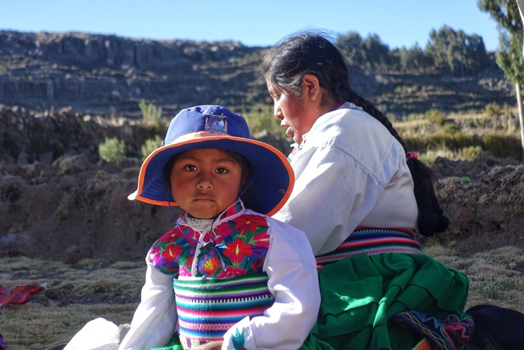 A curious child stares as her mother weaves on the island of Amantani in Lake Titicaca by Lori Zaino