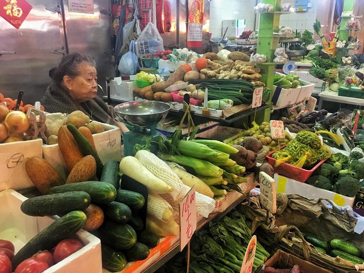 A woman selling veg in Hong Kong by Lori Zaino